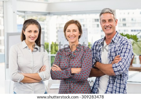 Portrait of smiling casual business people with arms crossed in the office - stock photo