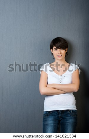 Portrait of smiling casual female posing isolated on grey background - stock photo