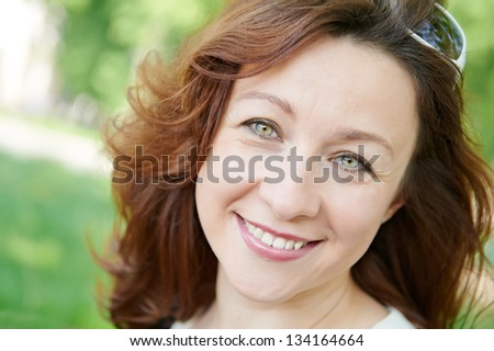 portrait of smiling caucasian brunette adult woman in spring cherry blossom tree garden outdoors - stock photo