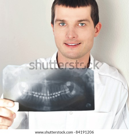 Portrait of smiling caucasian man doctor wearing uniform standing against wall at hospital looking at camera holding xray results of his patient - stock photo