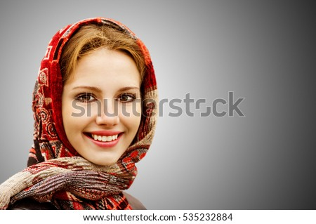 Portrait of smiling charming young woman in headscarf isolated on grey background.