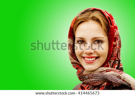 Portrait of smiling charming young woman in headscarf on a green background.
