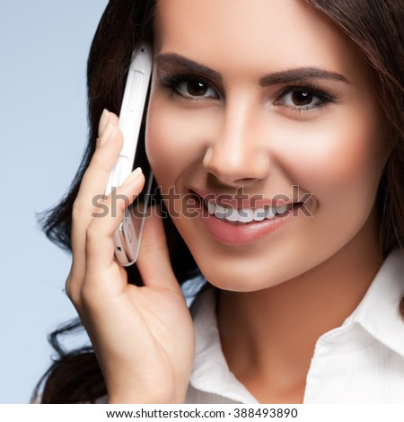 Portrait of smiling cheerful brunette businesswomen or customer support female phone operator with cell phone, against grey background. Consulting and assistance service call center. - stock photo