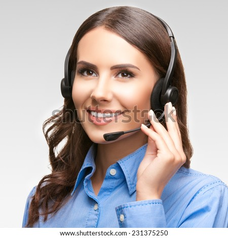 Portrait of smiling cheerful customer support phone operator in headset, against grey background - stock photo