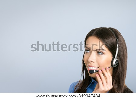 Portrait of smiling cheerful customer support phone operator in headset, against grey background