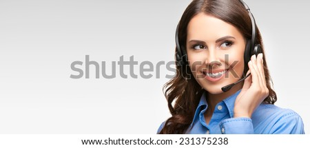 Portrait of smiling cheerful customer support phone operator in headset, with blank area for slogan, copyspace or product, against grey background - stock photo