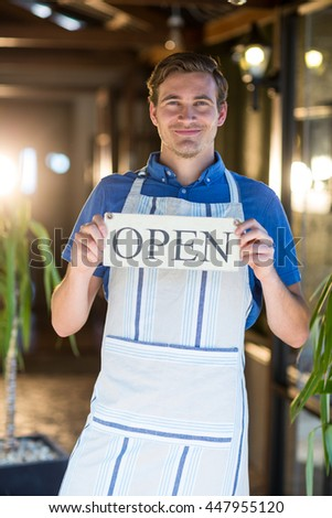 Portrait of smiling chef holding open sign in restaurant