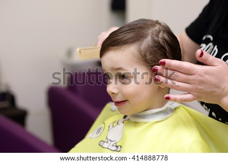 Portrait of smiling child at the barbershop - stock photo