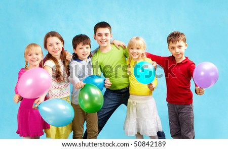 Portrait of smiling children holding balloons and embracing each other