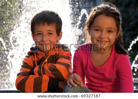 Portrait of smiling children in front the fountain - stock photo