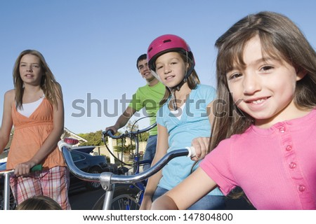 Portrait of smiling children with scooter and bicycles against sky - stock photo