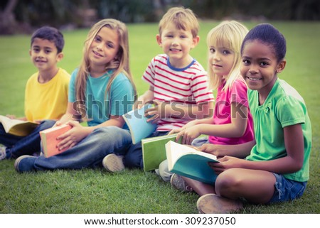 Portrait of smiling classmates sitting in grass and holding books on campus