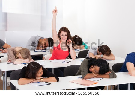 Portrait of smiling college student raising hand with classmates sleeping at desk in classroom