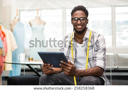 Portrait of smiling confident male fashion designer with digital tablet - stock photo