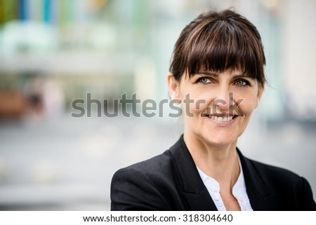 Portrait of smiling confident senior business woman in a street - stock photo