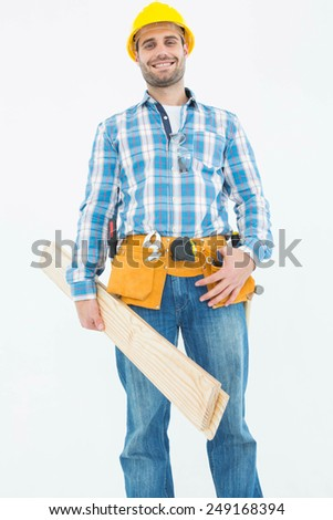 Portrait of smiling construction worker holding wooden planks against white background - stock photo