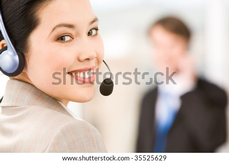 Portrait of smiling consultant with headset looking at camera