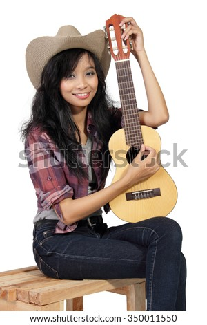 Portrait of smiling country girl sitting on a wooden chair with her small acoustic guitar, isolated on white background - stock photo