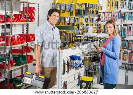 Portrait of smiling couple buying tools in hardware store