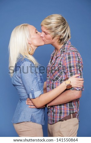 Portrait of smiling couple embracing on blue background - stock photo