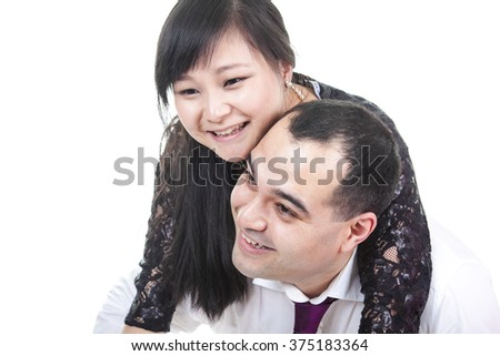 Portrait of smiling couple embracing on white background - stock photo
