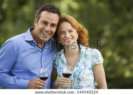 Portrait of smiling couple holding wine glasses in park - stock photo