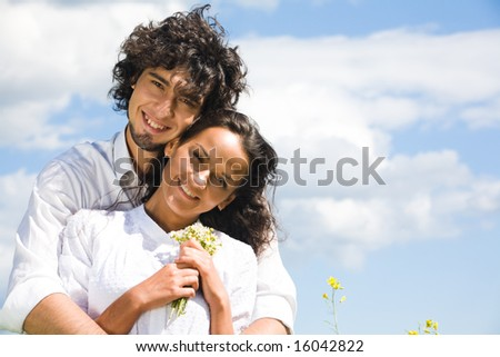 Portrait of smiling couple in white shirts on the background of sky - stock photo