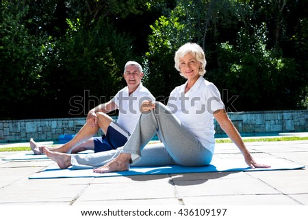 Portrait of smiling couple on exercise mat at poolside