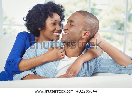 Portrait of smiling couple on the sofa looking at each other - stock photo