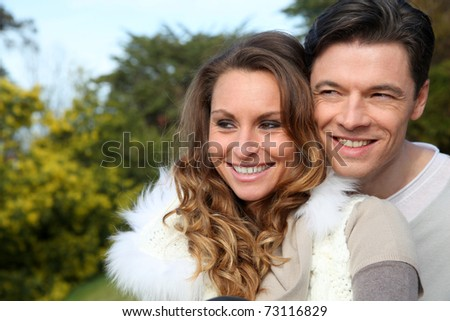 Portrait of smiling couple sitting outside on a sunny day - stock photo