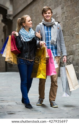 Portrait of smiling couple walking by street holding shopping bags