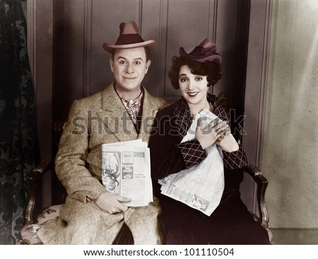 Portrait of smiling couple with newspapers - stock photo