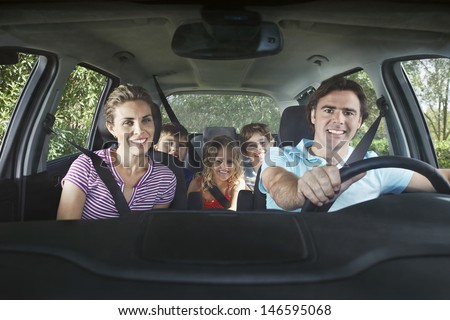 Portrait of smiling couple with three children in car - stock photo
