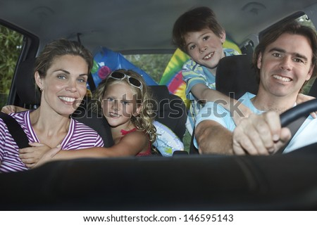 Portrait of smiling couple with two children in car