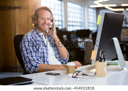 Portrait of smiling creative businessman working at computer desk in office