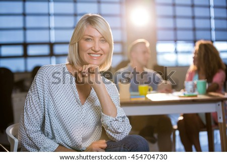 Portrait of smiling creative businesswoman with hand on chin sitting on chair at office - stock photo