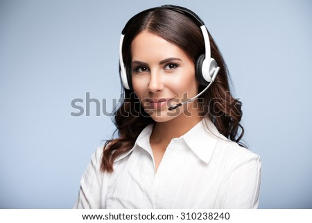 Portrait of smiling customer support female phone worker, against grey background. Consulting and assistance service call center. - stock photo
