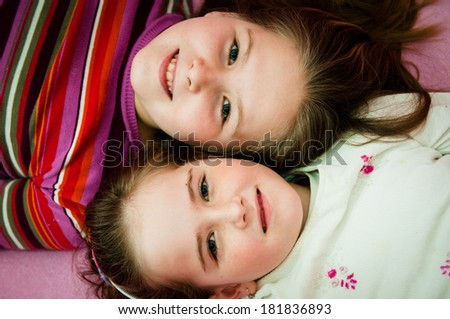 Portrait of smiling cute children (sisters) at home lying in bed