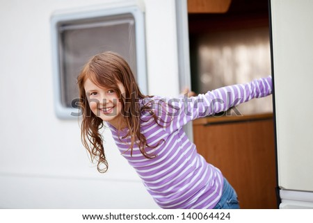 Portrait of smiling cute girl standing at caravan entrance - stock photo