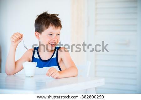 Portrait of smiling cute little boy refuses to eat delicious yogurt - stock photo