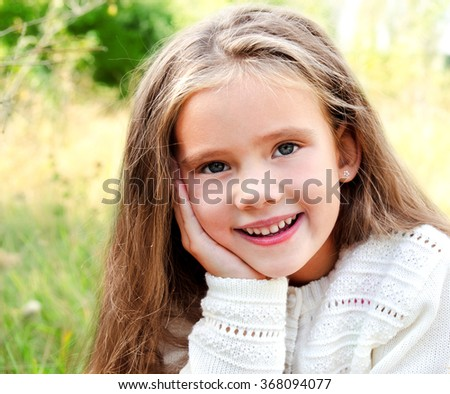Portrait of smiling cute little girl in summer day outdoor