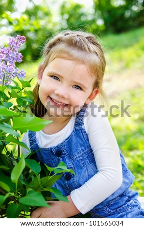 Portrait of smiling cute little girl outdoors on a summer day - stock photo