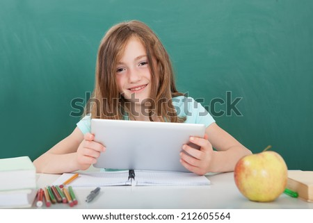 Portrait of smiling cute schoolgirl with digital tablet sitting at table against chalkboard - stock photo
