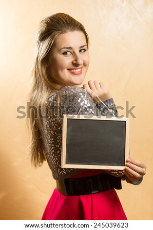 Portrait of smiling cute woman holding small blackboard