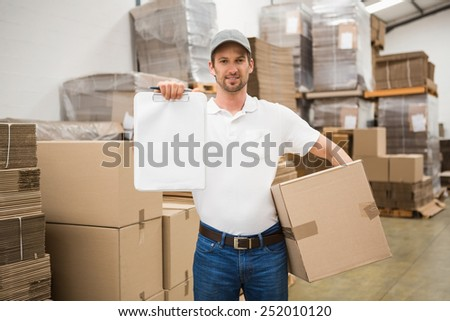 Portrait of smiling delivery man with box and clipboard in warehouse - stock photo