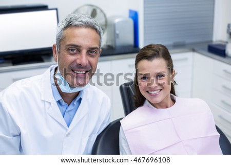 Portrait of smiling dentist and female patient at dentist clinic