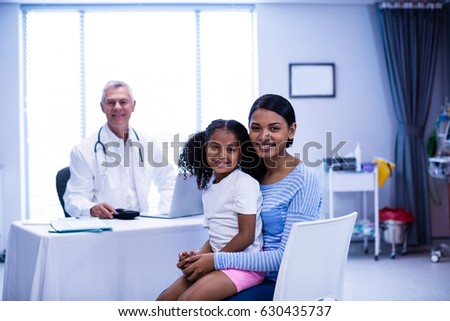 Portrait of smiling doctor and patient in clinic