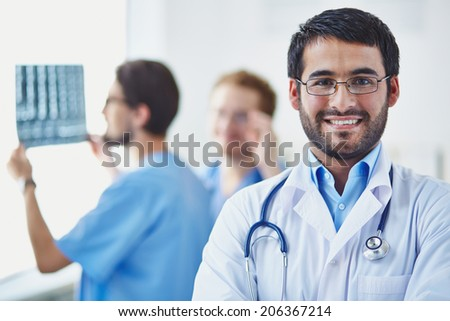 Portrait of smiling doctor looking at camera on background of his working colleagues - stock photo
