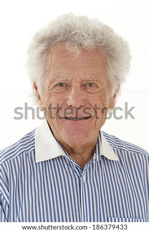 Portrait of smiling elderly man with white hair wearing striped shirt
