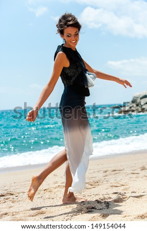 Portrait of smiling elegant brunette in designer dress on beach. - stock photo